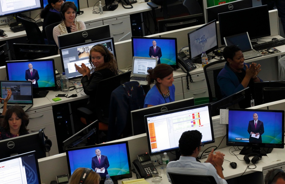 Journalists applaud in the newsroom as Al Jazeera America begins broadcasting in New York
